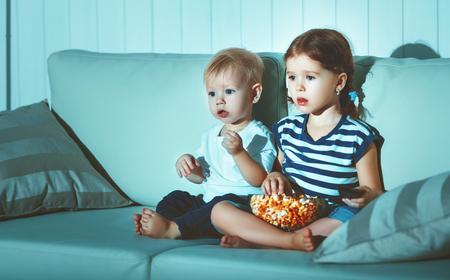 子供たちの兄と妹の夕方テレビを見て 写真素材