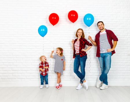 풍선과 함께 행복 한 가족입니다. 어머니, 아버지, 아들, 딸 흰색 빈 벽돌 벽 배경에 스톡 콘텐츠
