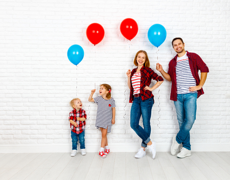 Happy family with ballons. mother, father, son, daughter on a white blank brick wall background