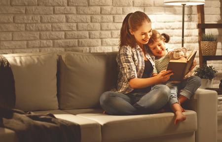 Family voordat je naar bed moeder leest aan haar kind dochter boek in de buurt van een lamp in de avond