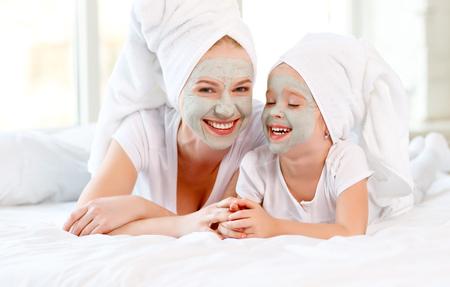 Gelukkige familie moeder en peuter maken gezicht huidmasker met handdoek op hoofd