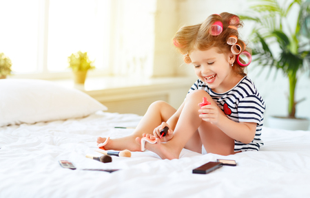 home: Happy funny child little girl with hair curlers does a pedicure, paints nails and laughs Stock Photo