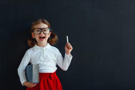 Gelukkig schoolmeisje voorschoolse meisje met boek in de buurt van schoolbord schoolbord