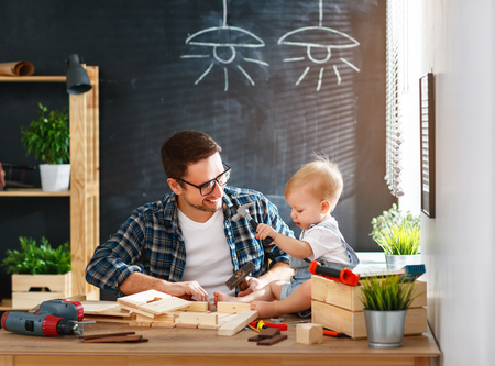 industry: Father and toddler son carved of wood in carpentry workshop Stock Photo