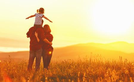 Gelukkige familie: moeder vader en kind dochter op de natuur bij zonsondergang Stockfoto