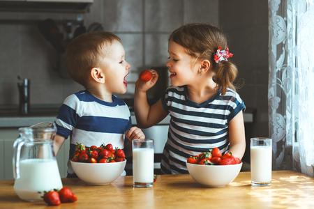 Gelukkige kinderen meisje en jongen broer en zus die aardbeien met melk eten Stockfoto