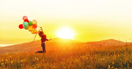 Gelukkig vrolijk meisje met ballonnen die over de weide loopt bij zonsondergang op de natuur in de zomer