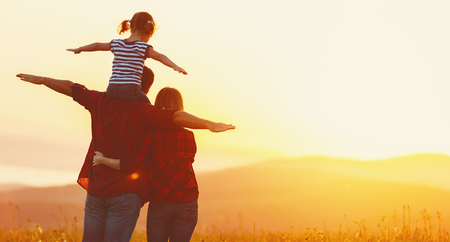 Happy family: mother father and child daughter on nature  on sunset