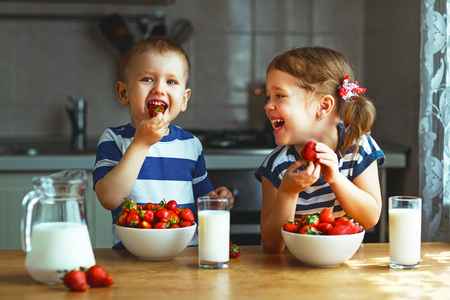 Happy children girl and boy brother and sister eating strawberries with milk Stock Photo