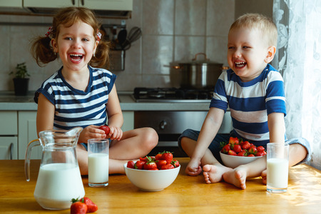 berry: Happy children girl and boy brother and sister eating strawberries with milk Stock Photo