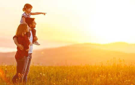 Glückliche Familie: Mutter Vater und Kind Tochter auf Natur auf Sonnenuntergang