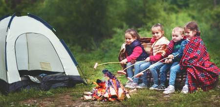 Kinder lachen und braten Würstchen auf dem Pfahl in der Nähe eines Zeltes in einer Wanderung Standard-Bild - 79547310