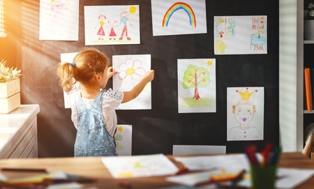 벽에 그녀의 그림을 매달려 아이 소녀