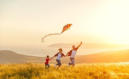 Glückliche Familie Vater der Mutter und Kind Tochter starten einen Drachen auf Natur bei Sonnenuntergang