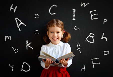 Happy schoolgirl preschool girl with book near school board blackboard