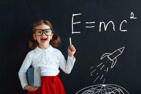 Child girl prodigy student with book near school blackboard