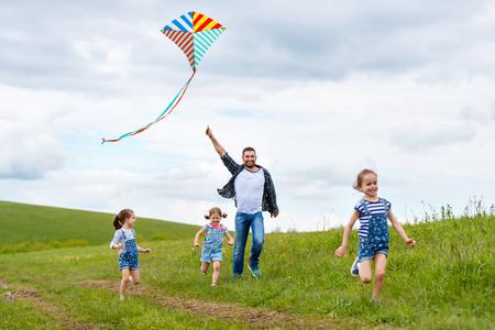 Feliz padre de la familia y los niños corren con una cometa en el prado de verano