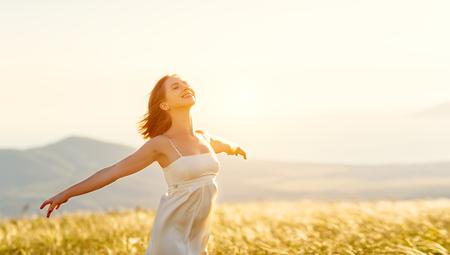Femme heureuse debout avec son dos sur le coucher de soleil dans la nature en été avec les mains ouvertes