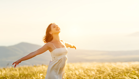 Gelukkige vrouw staande met haar rug op de zonsondergang in de natuur in de zomer met open handen Stockfoto - 80269115