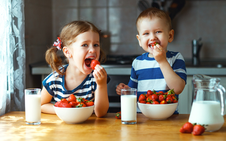Happy children girl and boy brother and sister eating strawberries with milk Фото со стока
