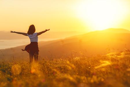 Felice donna in piedi con la schiena sul tramonto in natura in estate con le mani aperte Archivio Fotografico - 80405210