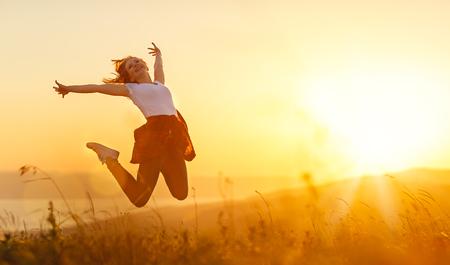 Gelukkige vrouw springen, verheugt zich, lacht op zonsondergang in de natuur