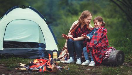 暖かい家族母と子娘テント キャンプで焚き火で手旅行します。