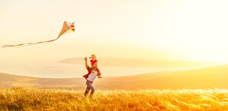 Glückliche Familie Vater und Baby Tochter laufen mit einem Drachen auf Wiese Standard-Bild - 80717425