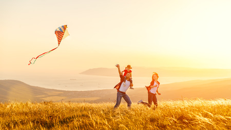 어머니와 아이 딸의 행복 한 가족 아버지 일몰에 자연에 연을 시작 스톡 콘텐츠