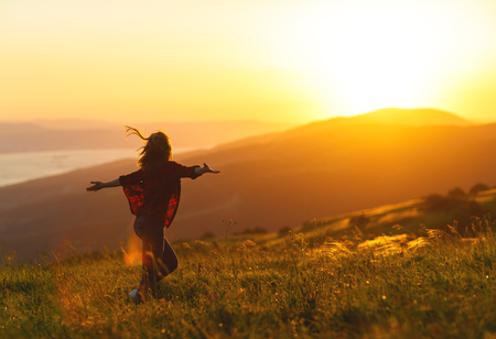 Happy woman with open hands dances,  rejoices, laughs  on sunset in nature