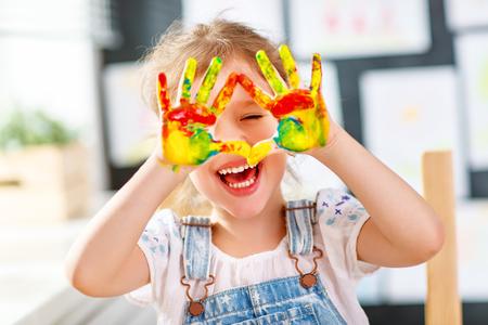 Gelukkig grappig kindmeisje trekt lachende shows handen vies met verf