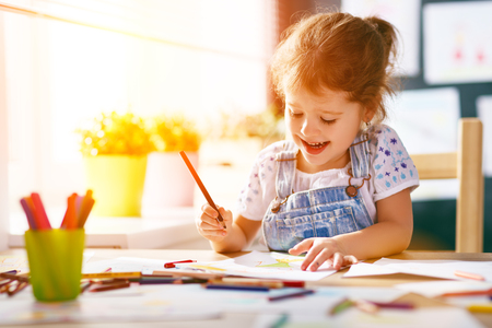 child  girl draws with colored pencils in kindergarten
