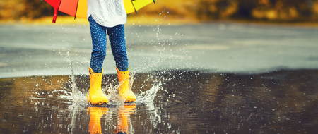 Feet of child in yellow rubber boots jumping over a puddle in the rain Stockfoto