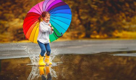 Glückliches lustiges Ba-Kind durch Mädchen mit einem mehrfarbigen Regenschirm, der auf Pfützen in den Gummistiefeln und im Lachen springt Standard-Bild