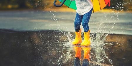 Pies de niño en botas de goma amarillas saltando sobre un charco en la lluvia