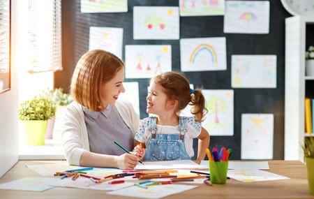 幼稚園での創造性で従事している母と子の娘描画 写真素材