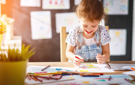 child  girl draws with colored pencils in kindergarten  Stock fotó