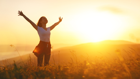 Happy woman   on the sunset in nature in summer with open hands  Banco de Imagens