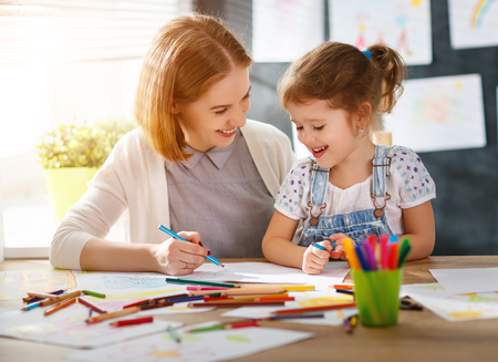 mother and child daughter draws are engaged in creativity in kindergarten