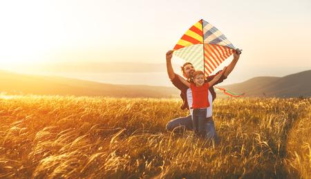 Gelukkige familievader en baby dochter lanceren een vlieger op weide