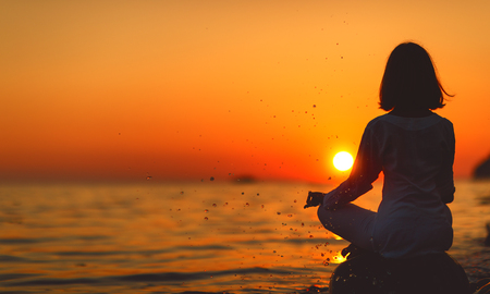woman practices yoga and meditates in the lotus position on sunset beach Stock fotó - 83649084