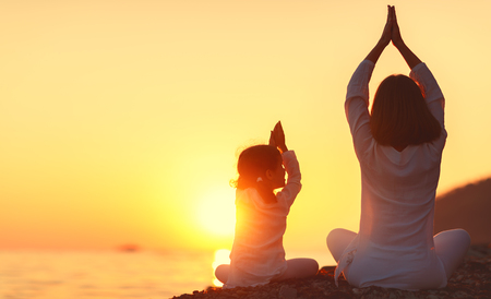 Happy family mother and child daughter doing yoga, meditate in lotus position on beach at sunset Foto de archivo