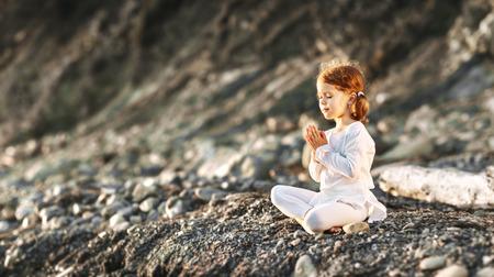 행복한 아이 소녀 meditates 연꽃 위치에 여름 요가 야외에서 약혼 스톡 콘텐츠