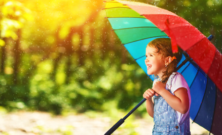 drop water: Happy child girl laughs and plays under the summer rain with an umbrella
