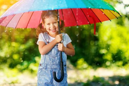 幸せな子少女笑うし、傘と夏の雨の下で遊ぶ