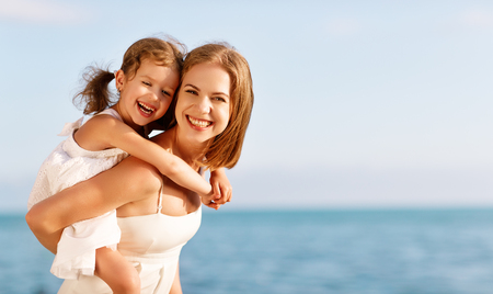 happy family at the beach. mother hugging child daughter