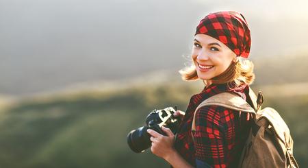 夏の屋外のハイキング中に夕暮れ時の山の上にカメラを持つ女性観光カメラマン