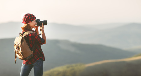 Woman tourist photographer with camera on top of a mountain at sunset outdoors during a hike in summer