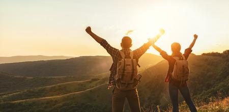 Gelukkige paar man en vrouw toerist op de top van de berg bij zonsondergang buitenshuis tijdens een wandeling in de zomer