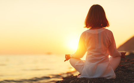 woman practices yoga and meditates in the lotus position on sunset beach Stock fotó - 82592554